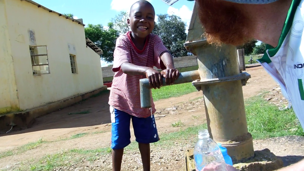 A kid helping me fill water bottles from a well