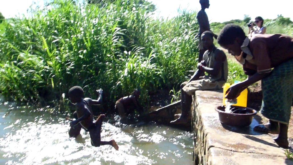 A young girl washing clothes as kids dive bomb into the river
